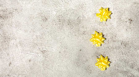 Yellow gift bow on concrete background template for posters and banners