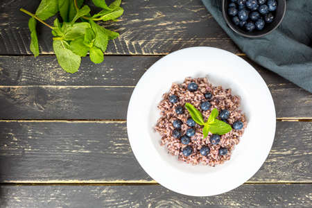 Delicious risotto with blueberries served on dark wooden table, flat lay