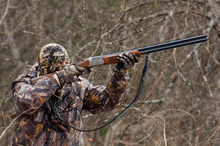 inconspicuous: hunter in camouflage takes aim from a gun