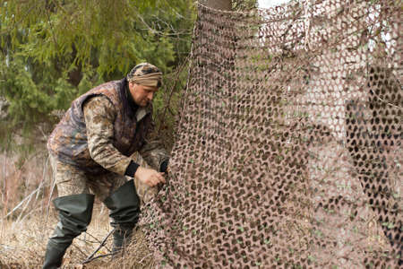 hunter places camouflage netting