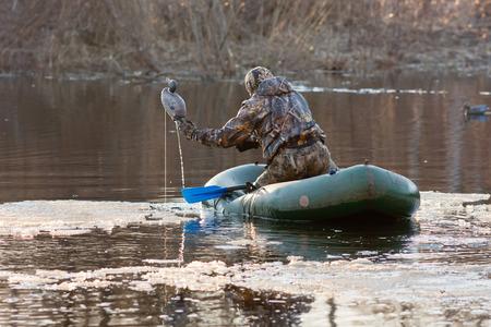 Le chasseur met canards en peluche sur l'eau d'un bateau de caoutchouc Banque d'images - 28909300