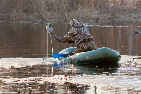 the hunter puts stuffed ducks on water from a rubber boat   Imagens