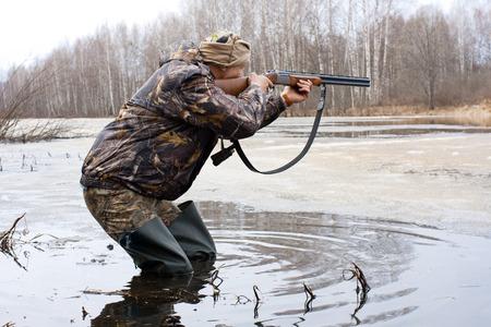 hombre disparando: el cazador dispara el juego de una pistola