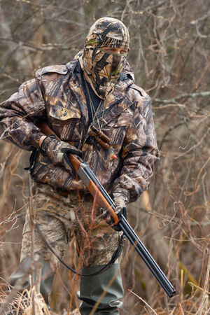 inconspicuous: the hunter in camouflage with a gun Stock Photo