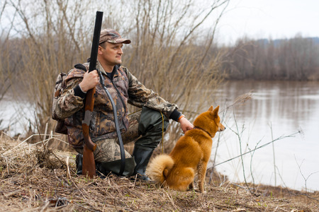 the hunter with a gun and a dog sits on the shore