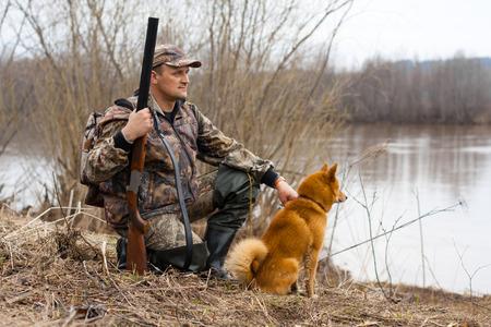 cazador: el cazador con un arma y un perro se sienta en la orilla