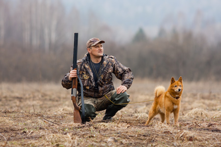 the hunter sits with a dog on the field and look out for duck