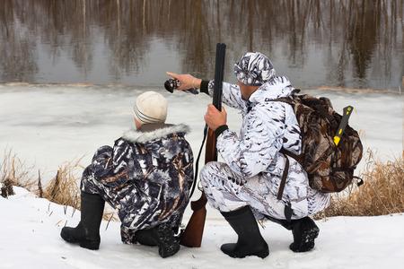 jager toont zijn zoon waar de prooi op de rivier