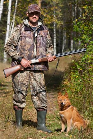 jager met hond op de bosweg Stockfoto