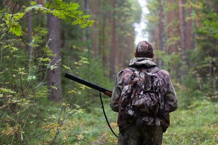 Chasseur marchant avec un pistolet sur la route de la forêt Banque d'images - 34841644
