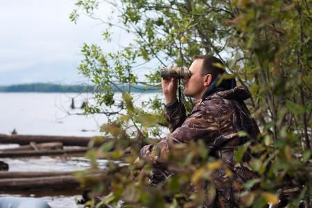 jager kijkt door een verrekijker bij de rivier