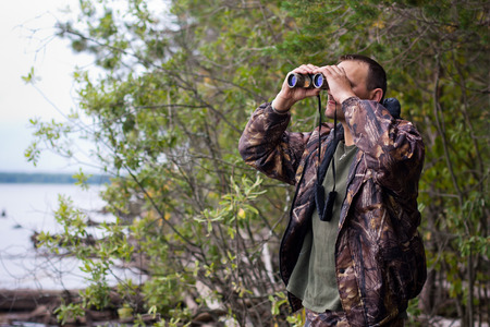 hunter man: hunter looking through binoculars on the river