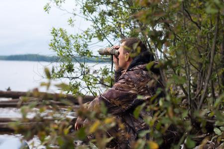 jager kijkt door verrekijker op de rivier Stockfoto