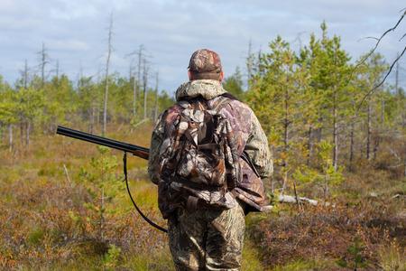 the hunter: cazador caminando con el arma en el pantano