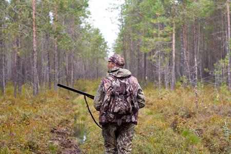 jager die met kanon op de bosweg loopt