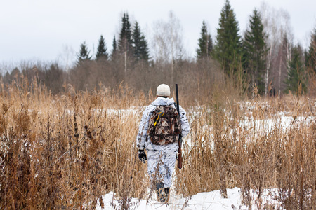 hunter with gun on the snowy field