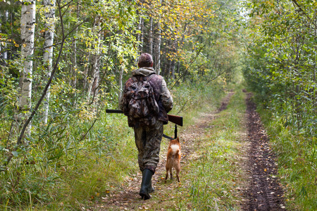 hunter with dog and gun walking on the forest road