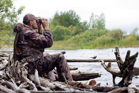 cazador: cazador mirando a través de binoculares en el río