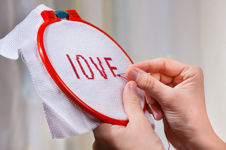 hands embroider a word love photo