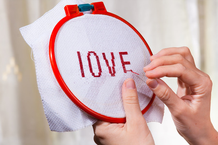 hands embroider a word love