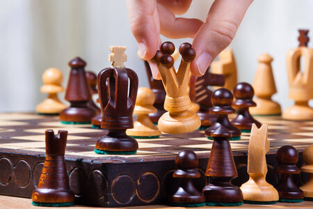 chess player: the hand of chess player with queen