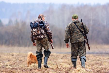 the hunter: dos cazadores y perro en el campo Foto de archivo