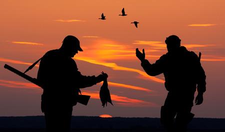 Silhouette von zwei Männer auf der Jagd