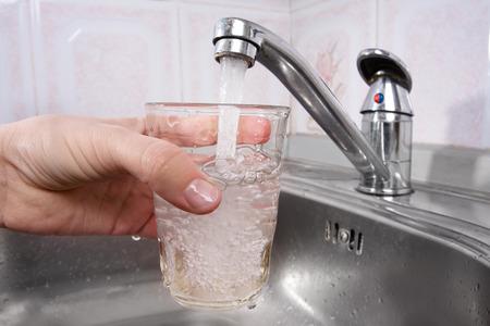 grifos: Mano que sostiene un vaso de agua vertida de grifo de la cocina Foto de archivo