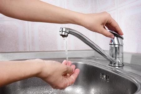 llave agua: A su vez la mano en un grifo Foto de archivo