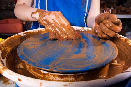 alfarero: Potter limpia la rueda de la cer�mica Foto de archivo