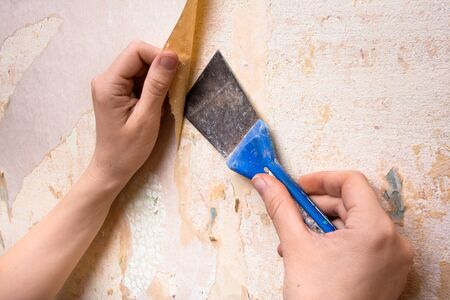 scrape: removal of old wallpapers with spatula Stock Photo