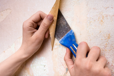 removal of old wallpapers with spatula Stock Photo