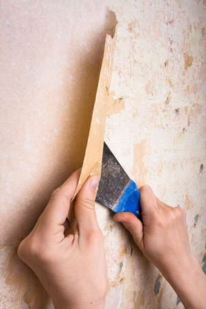 hands removing wallpaper from wall photo