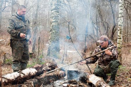 twee jagers eten koken boven een kampvuur