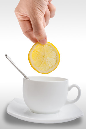 hand puts a slice of lemon in �up of tea photo
