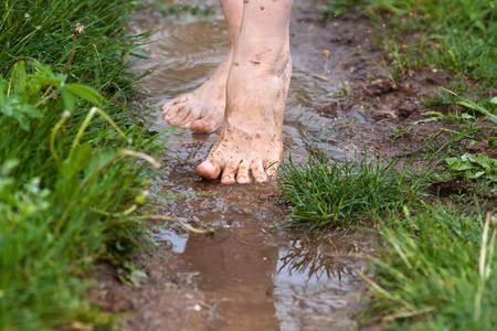 voeten van een jonge vrouw op blote voeten lopen door de plassen