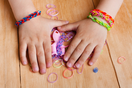 kids weaving: child hands with rubber bands on the wooden table Stock Photo
