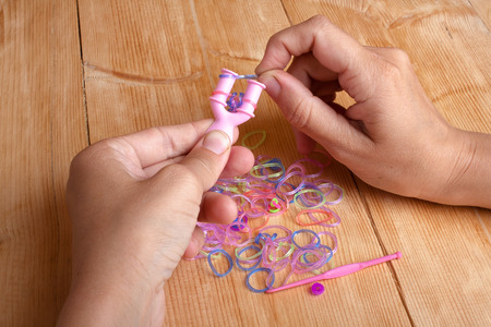 y shaped: hands making rubber band bracelet with crochet and Y-weaver on the wooden table