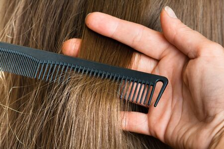 strand of hair: hand of hairdresser holding strand of hair and comb, closeup Stock Photo