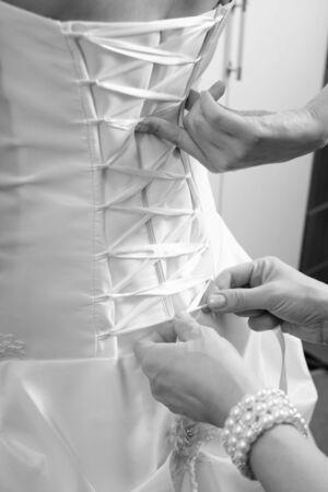 bride bangle: hands of bridesmaid lacing corset on wedding dress, closeup