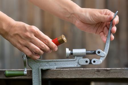 reloading: reloading cartridge by shotgun shell reloader, closeup