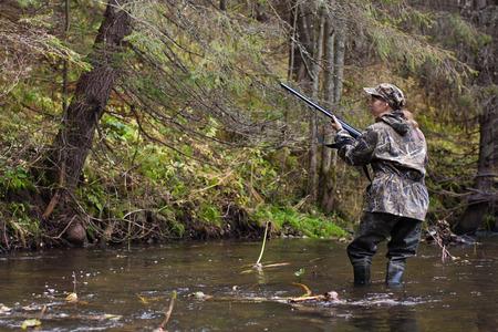 cazador: Mujer cazador en camuflaje con el arma en el río Foto de archivo
