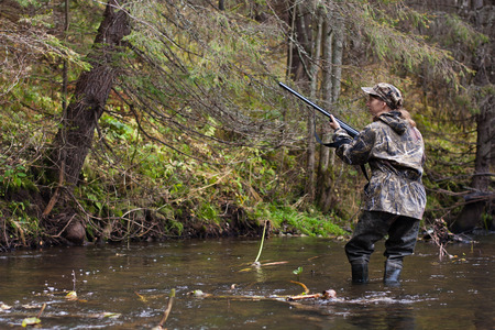 waders: Woman hunter in camouflage with gun on the river Stock Photo