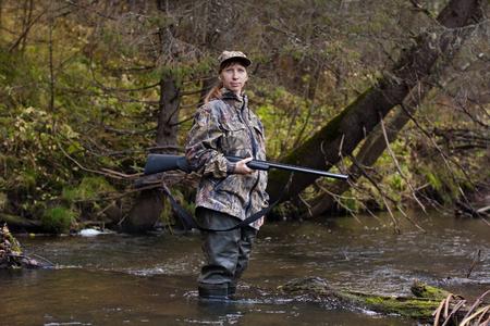 botas altas: Mujer cazador en camuflaje con el arma en el río Foto de archivo