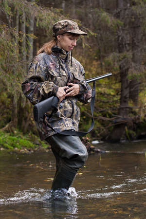 bank activities: Woman hunter in camouflage with gun crossing the river