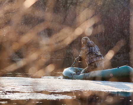 duck hunting: hunter on the rubber boat during duck hunting