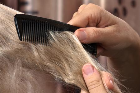 combing hair: hands of woman combing hair her daughter, closeup