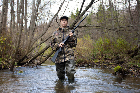 camouflage woman: Woman hunter in camouflage with gun on the river Stock Photo