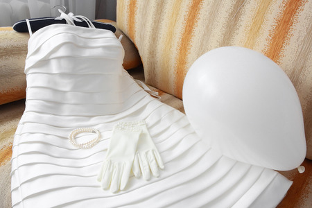 bride bangle: wedding dress with accessories and toy balloon laying on the sofa Stock Photo