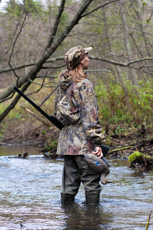 decoy: Woman hunter in camouflage with gun and stuffed duck on the river Stock Photo